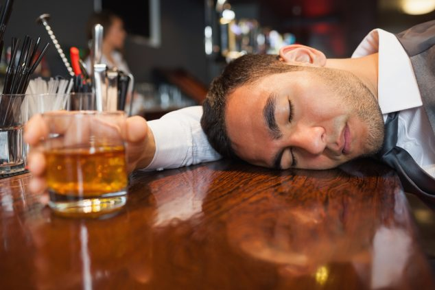 Drunk and unconscious businessman lying on a counter