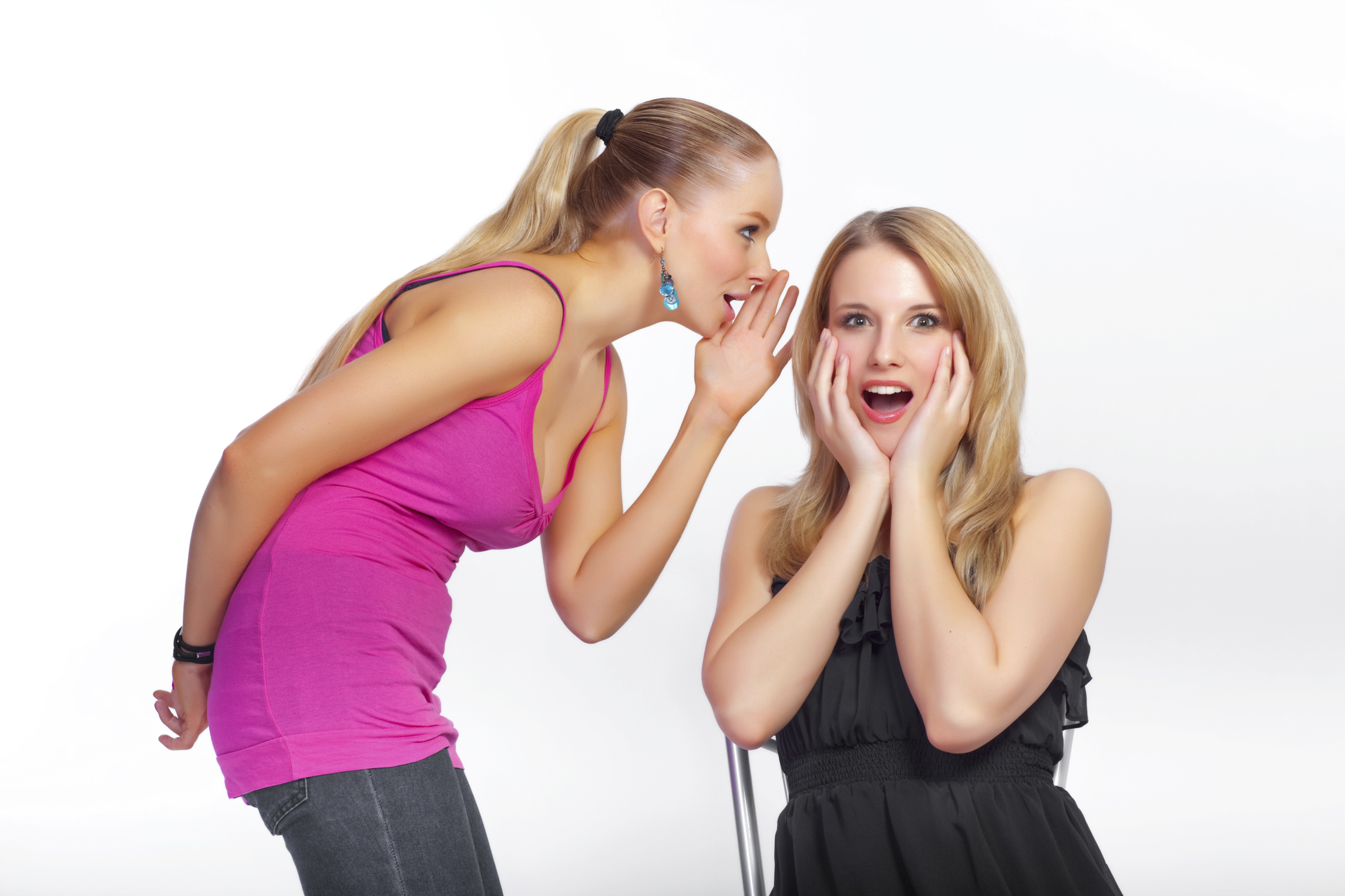 A young girl whispers a secret into her friends ear