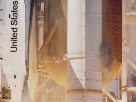 Camera D-67 shows grey smoke near the aft attach strut on the right SRB.