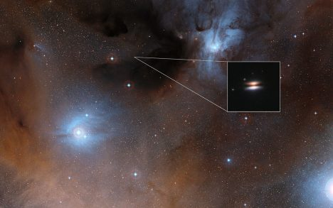 The young star 2MASS J16281370-2431391 lies in the spectacular Rho Ophiuchi star formation region, about 400 light-years from Earth. It is surrounded by a disc of gas and dust — such discs are called protoplanetary discs as they are the early stages in the creation of planetary systems. This particular disc is seen nearly edge-on, and its appearance in visible light pictures has led to its being nicknamed the Flying Saucer. The main image shows part of the Rho Ophiuchi region and a much enlarged close-up infrared view of the Flying Saucer from the NASA/ESA Hubble Space Telescope is shown as an insert.