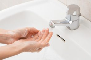 41263293 - closeup shot of a woman washing hands with soap lather over bathroom sink. girl cleaning hand.