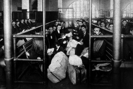 A group of immigrants waiting in a holding pen to be examined by doctors, Ellis Island c.1902.