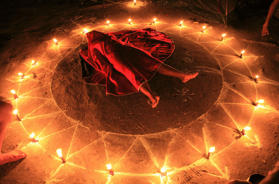 A night ritual begins.  The participant is placed inside the oracle to induce a trance-state and covered in a red shroud, symbolizing the nature of the spirit to be invoked.  The arrows point outward to the many directions the spirit must take on its difficult journey.