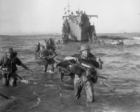 Infantry from the 51st Highland Division wade ashore from a landing ship, 10 July 1943.
