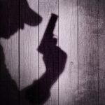 Gangster or investigator or spy silhouette on natural wooden wal