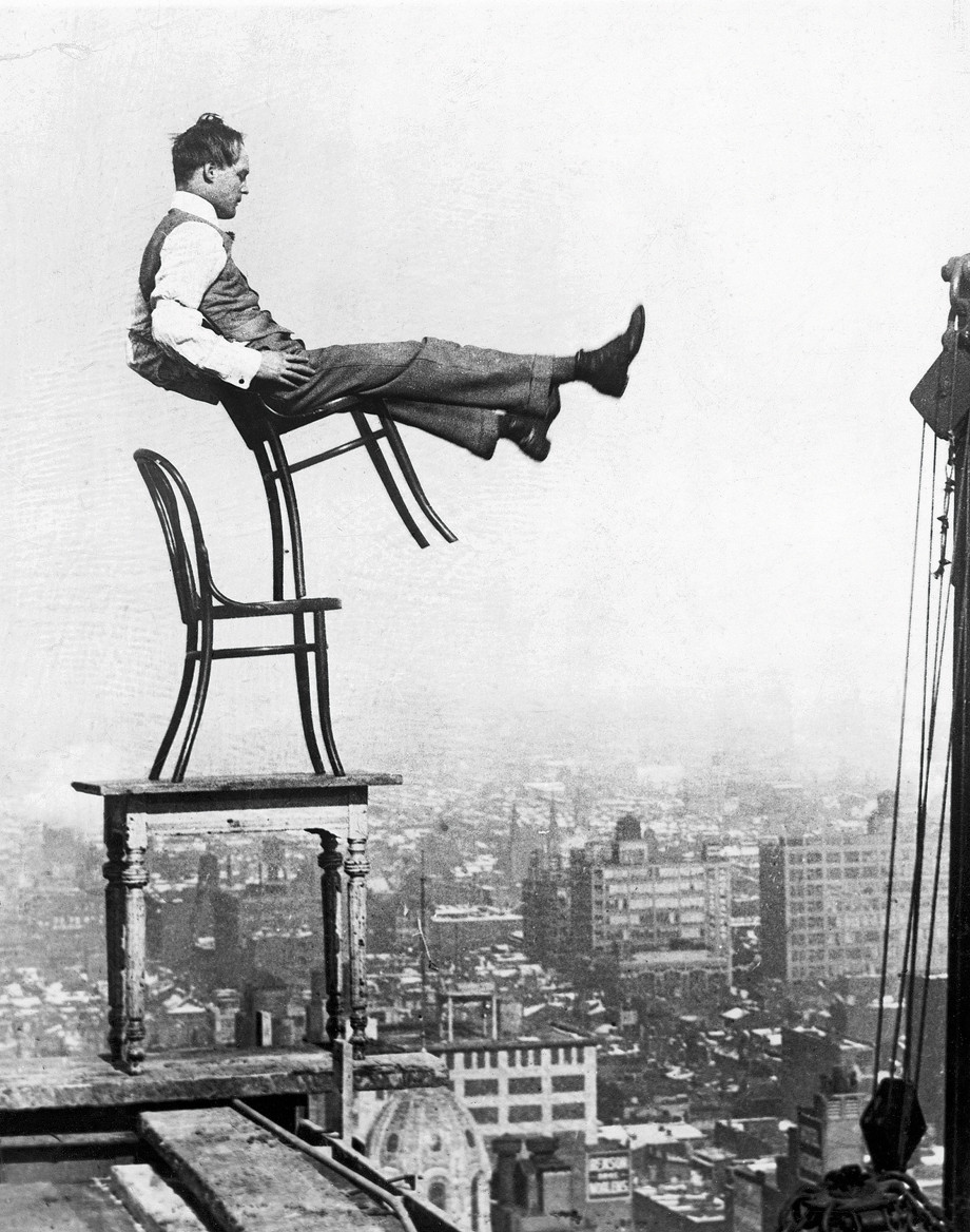 ca. 1920s --- Perched on a girder at the edge of a building under construction, a confident daredevil balances on the back legs of a chair atop another chair set on a table, from a height of 20 stories - without a safety net. --- Image by © Underwood & Underwood/Corbis