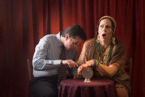 Female fortune teller shielding man from looking at crystal ball